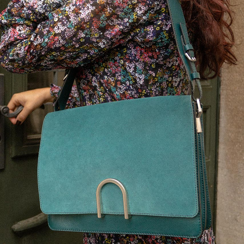 A blue shoulder bag worn with a flower dress.