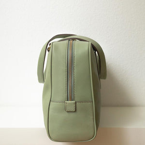 A pistachio green handbag from left.