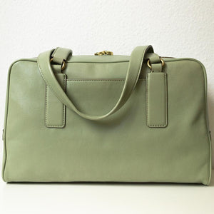 A pistachio green handbag from the back.