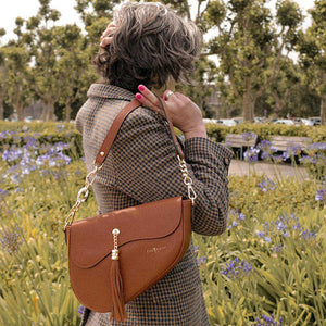 A woman wearing a brown jacket and saddle bag.