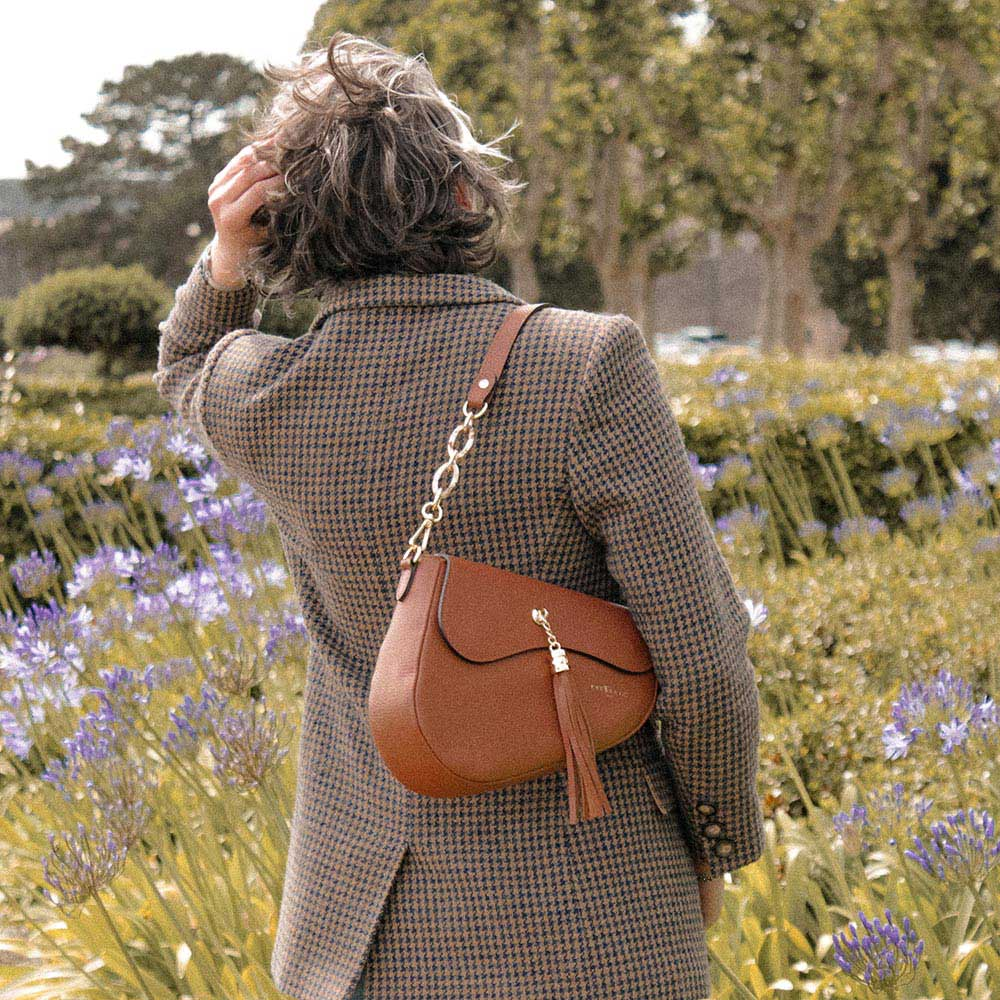 A woman standing in a park with a saddle bag.