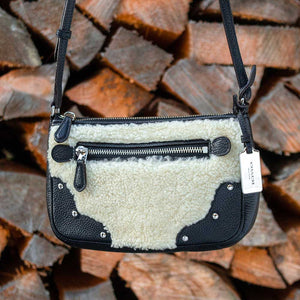 A shearling bag in front of chopped wood.