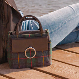 A tartan bag worn with blue jeans.