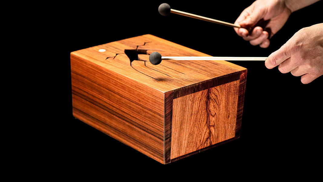 Hands playing a 5-key wooden tongue drum with mallets