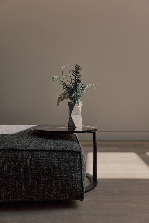 Handmade concrete vase from Mexico styled in a living room scene