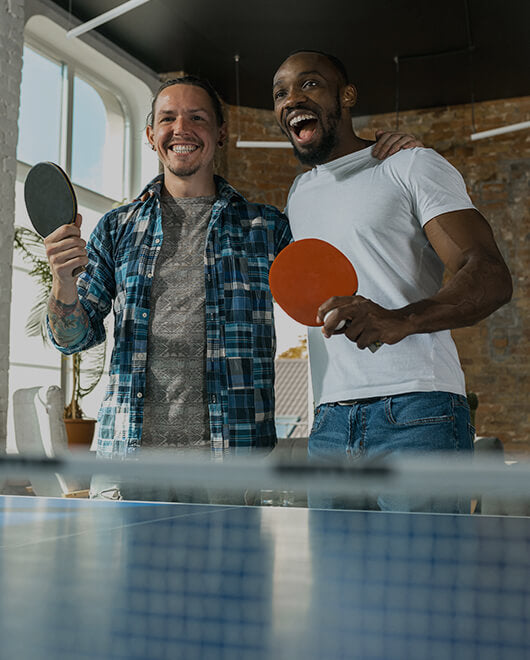 Two teammates playing table tennis and laughing