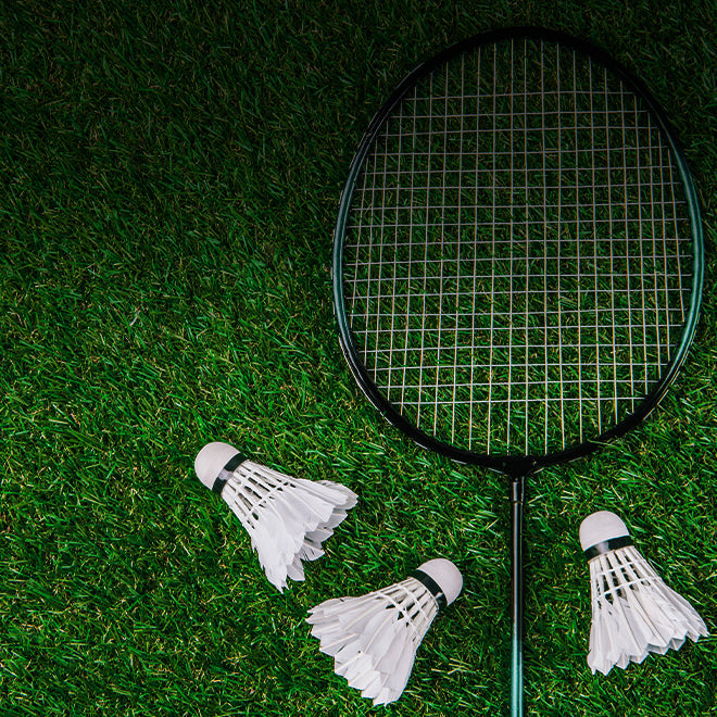 badminton racquet and shuttlecocks in the grass