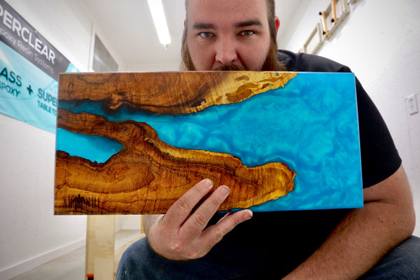 Jon holding a wood and blue resin board in front of his face