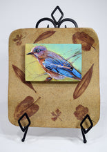 Load image into Gallery viewer, Backyard Bluebird painting by Pat Cross mounted in a handbuilt and kiln fired stoneware frame resting on a black metal easel.