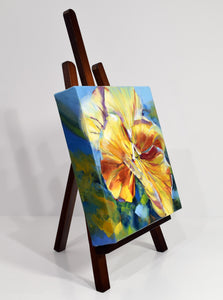 Sunny Petunia original oil painting on display easel facing right by Pat Cross.