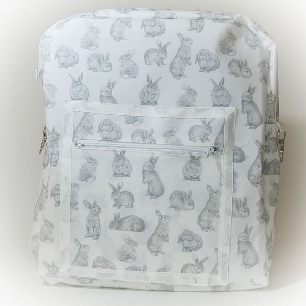 Front view of backpack with grey bunny design on white bag showing front zip pocket detail.