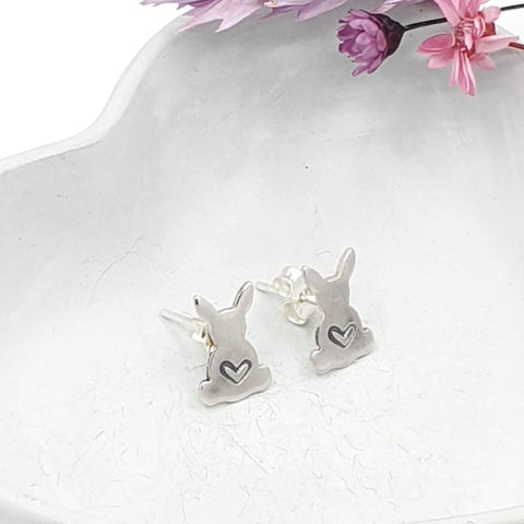 Silver stud earrings in the shape of a rabbit with a love heart engraved in the middle.