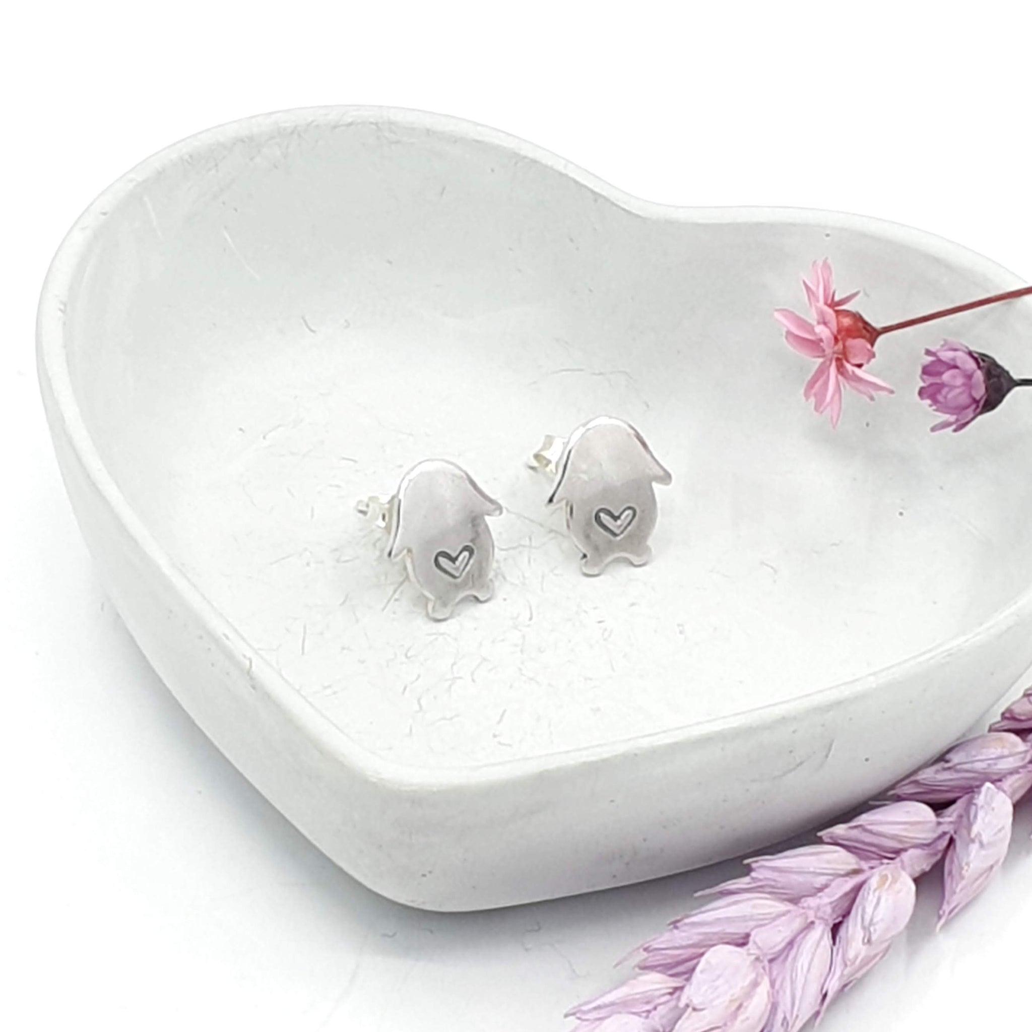 Silver stud earrings in the shape of a lop bunny. A love heart is engraved in the middle of each earring.