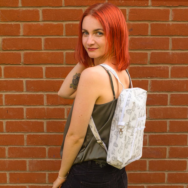 Red haired model looks over left shoulder with bunny backpack on.