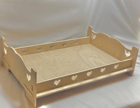 Wooden pet rabbit bed frame with two hearts cut out on the decorative head and foot boards. Five hearts are cut on each side of the bed.