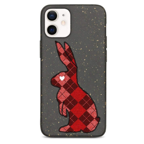 Black phone case with speckled texture. Picture of a sideways rabbit silhouette with a red arygle pattern and a white love heart for an eye.
