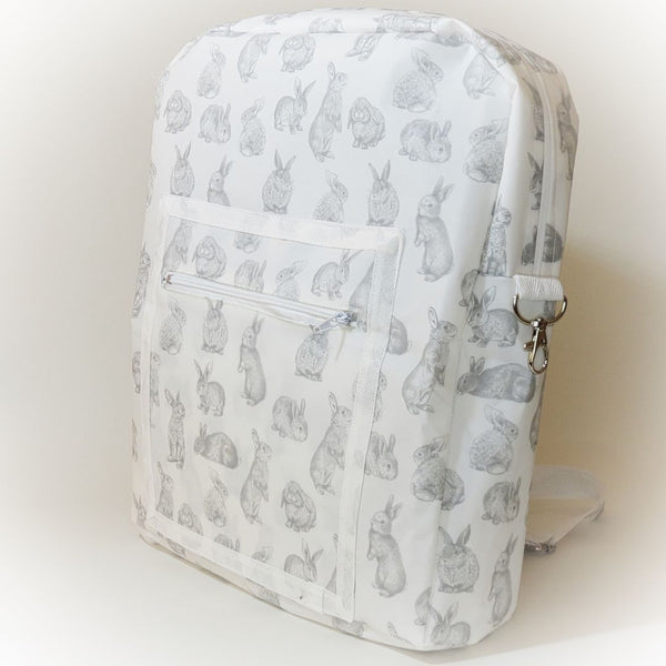 Side view of backpack with grey bunny design on white bag