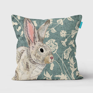 Cushion with a picture of a wildwood rabbit and flowers on it.