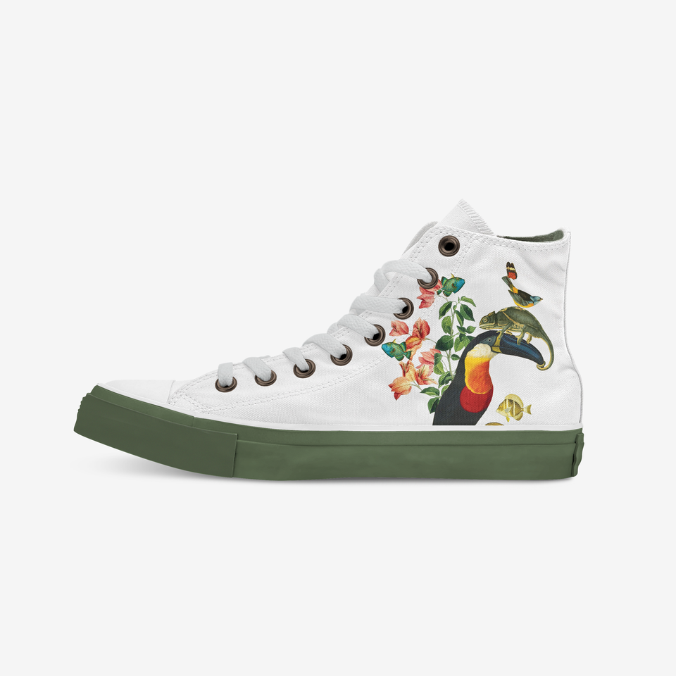 White sneaker view from the inner side. From this angle we see the same toucan, reptile and bird from the other side of the shoe but this time from the right angle, also accompanied by colorful plants and flowers by their side. The holes where the white shoelaces are placed are covered with a copper color metal ring. The shoe sole shows a full green khaki.