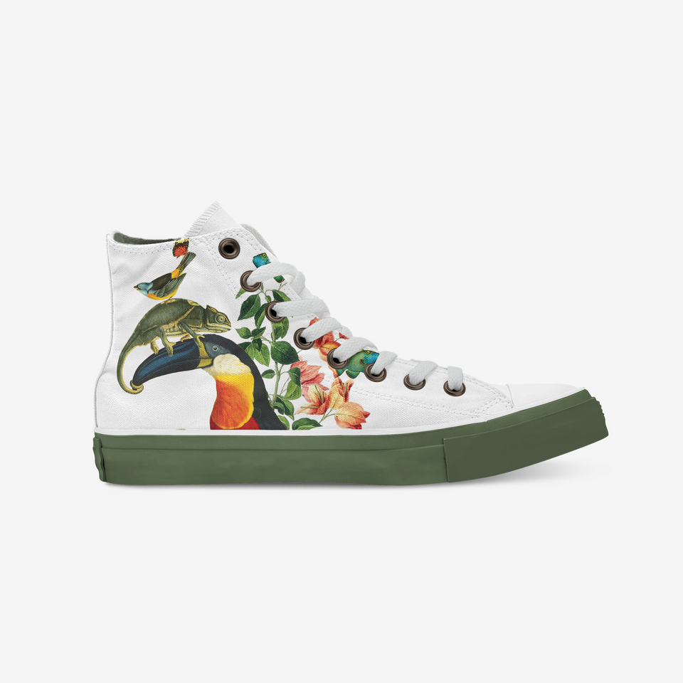 White sneaker view from the side that shows an illustration of a shows a toucan seen from the left side that has a reptile above its beak and this reptil has a colorful bird above him. Next to them there is a bunch of green and pink with a little yellow flowers and plants. The holes where the white shoelaces are placed are covered with a copper color metal ring. The shoe sole is all in khaki green.