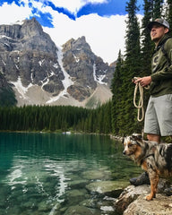 Man and dog standing by lake with mountains in the background
