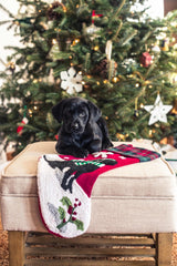 puppy sitting on a stocking in front of a Christmas tree