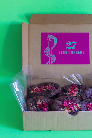 Dark chocolate vegan cookies with raspberry pieces and peanut butter in a box from 27 Vegan Bakery