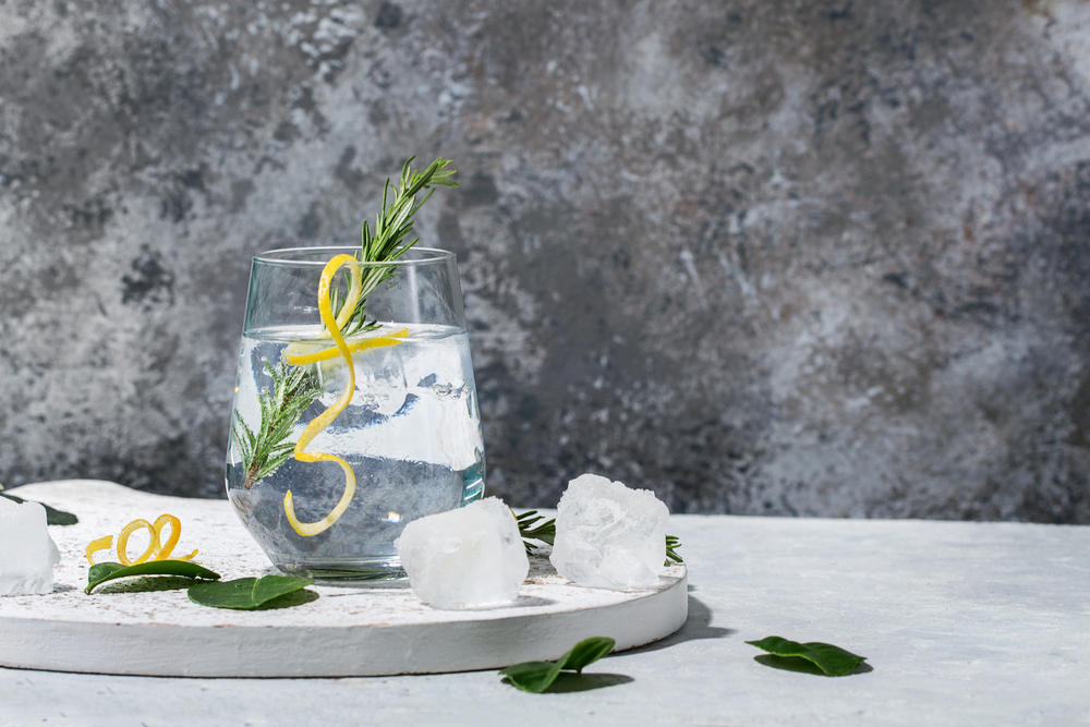 Gin and Tonic drink served with ice, lemon zest and fresh rosemary.