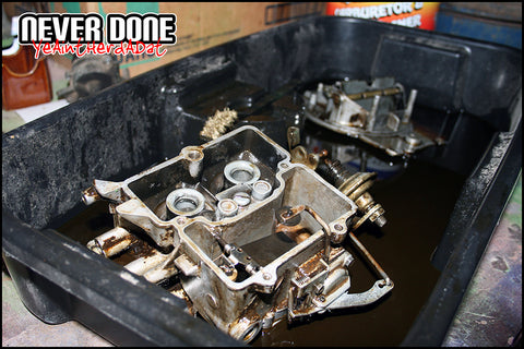 cleaning a carburetor in a plastic tray