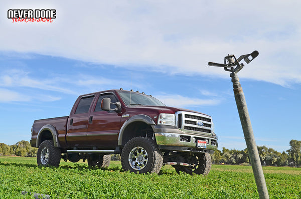 "lifted red Ford F350 Super Duty in a field with chrome rims and 37"" mud tires"