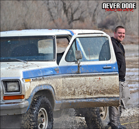 Clint Grover getting out of water logged bronco with water rushing out of door and mud covering the outside