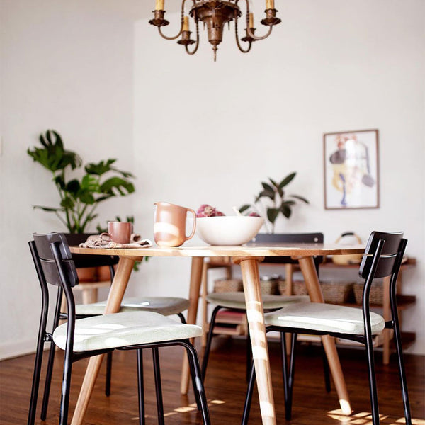 Black sherman chairs at a light wooden table under a brass chandelier partially in frame.