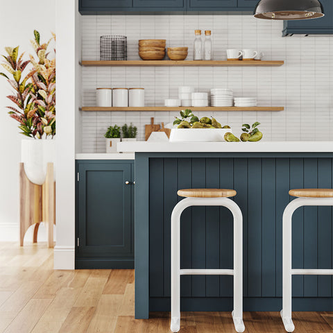 Two modern sir burly stools with chunky white steel legs and circular natural wood seats at a blue painted island. blue shaker cabinets and white subway tile backsplash in the background
