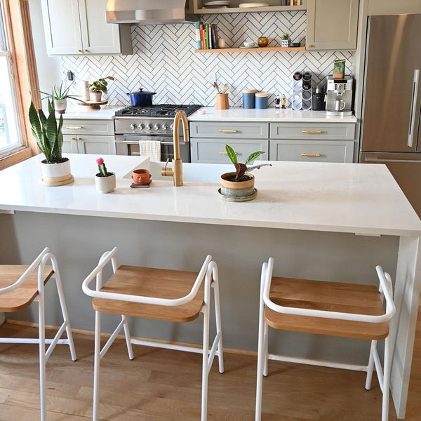 Three white steel half hurdle bar stools at a white kitchen island that has a sink and potted plants on it. Stove and cabinets in the background with white tile backsplash. Brass details throughout.