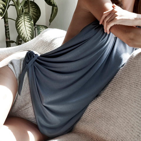 Woman laying comfortably on a couch wearing a convertible long titanium blue shirt