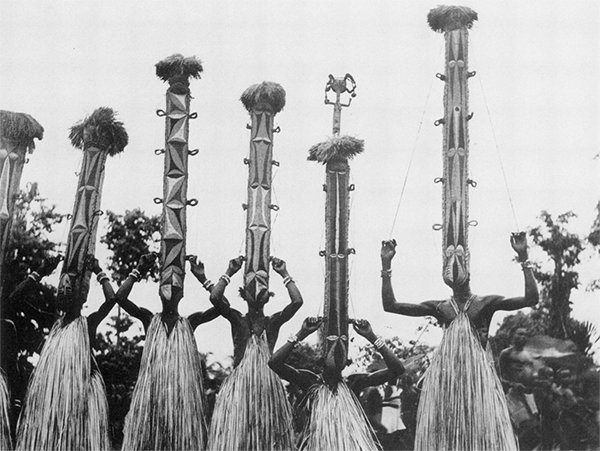 Igbo initiates wearing tall masks made from calabash.