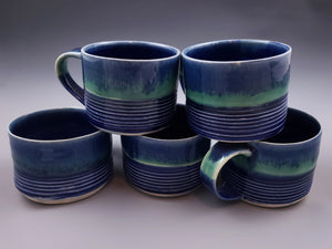 stack of blue and green cafe mugs