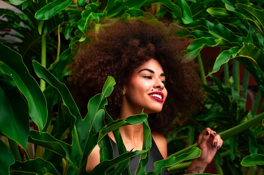 Woman with curly hair in front of a palm tree