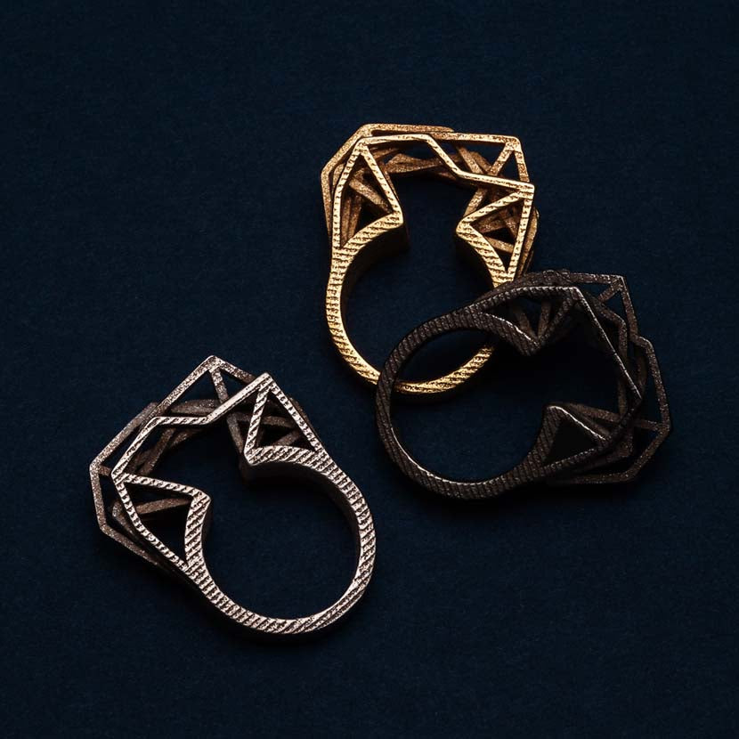 3D printed steel ring with gold and bronze variants.