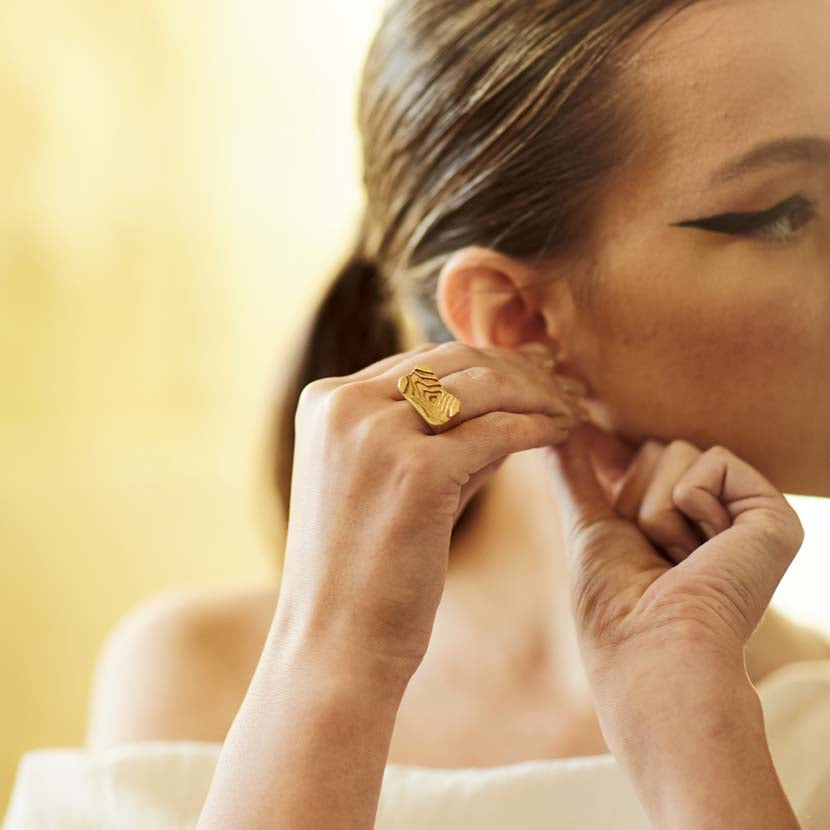 Woman wearing architectural rings putting and earring on.