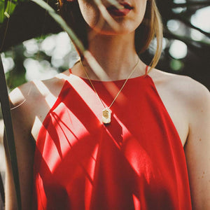 Architecture necklace with woman wearing red dress.
