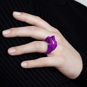 Woman shows a purple big statement ring.
