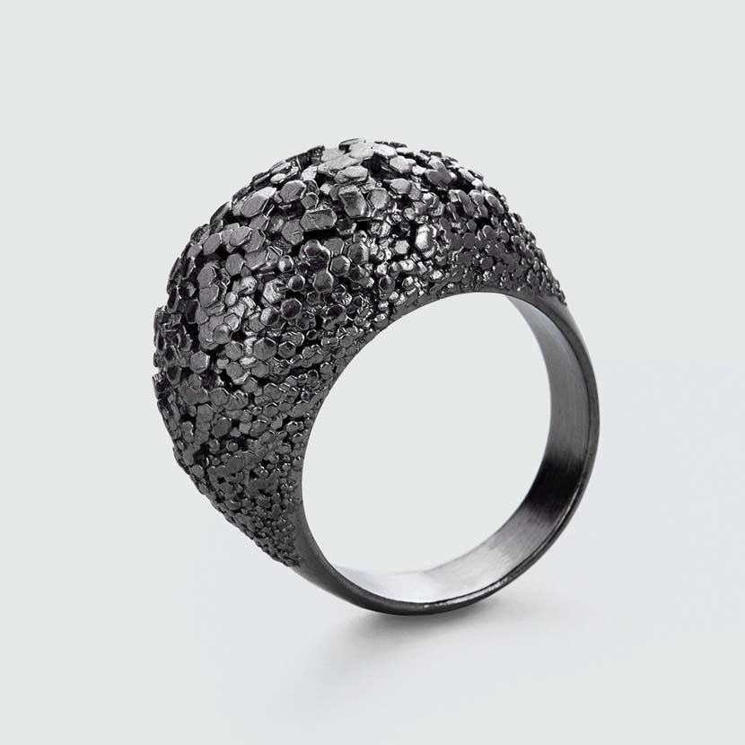 Black crystal ring with detailed surface.