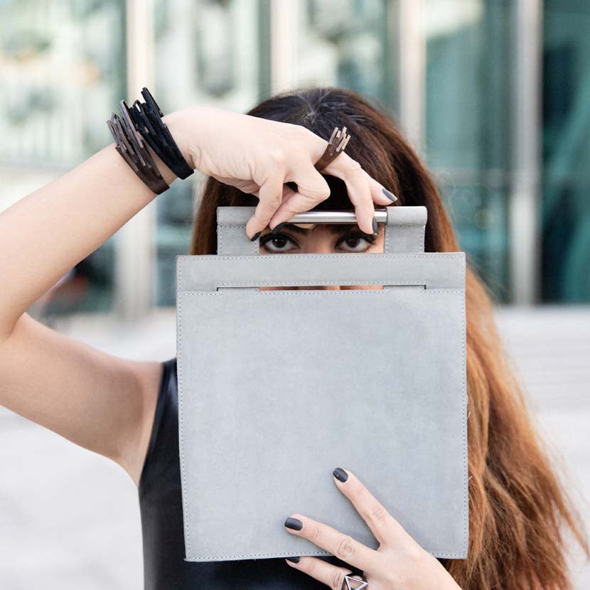 Black cuff bracelet presented by model hiding behind a bag.