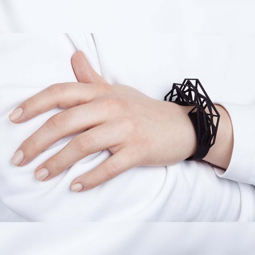 Black cuff bracelet on wrist of woman.