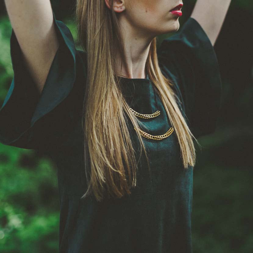 Geometric double necklace demonstrated by model.
