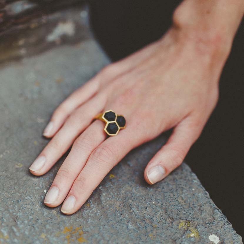 Geometric ring gold black on finger in front of concrete wall.