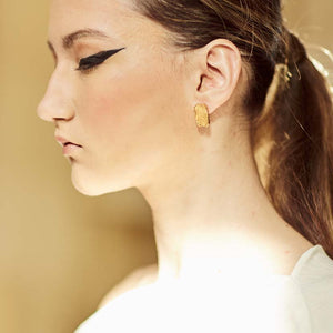 Gold architectural earrings on Maltese woman during Fashion Show.