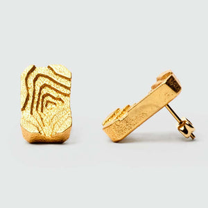 Gold architectural earrings with gold studs.