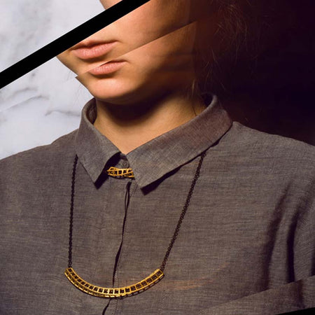 Gold double necklace on woman with blouse.